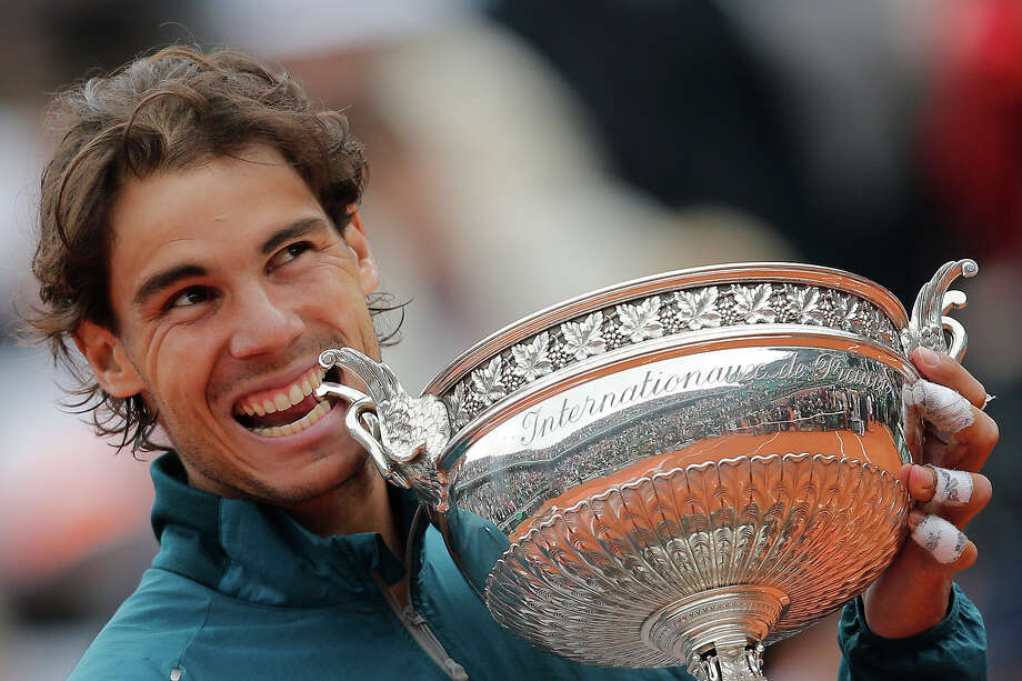 Spain's Rafael Nadal bites the trophy after winning against compatriot David Ferrer in three sets 6-3, 6-2, 6-3, in the final of the French Open tennis tournament, at Roland Garros stadium in Paris, Sunday June 9, 2013. Photo: Christophe Ena, ASSOCIATED PRESS / AP2013
