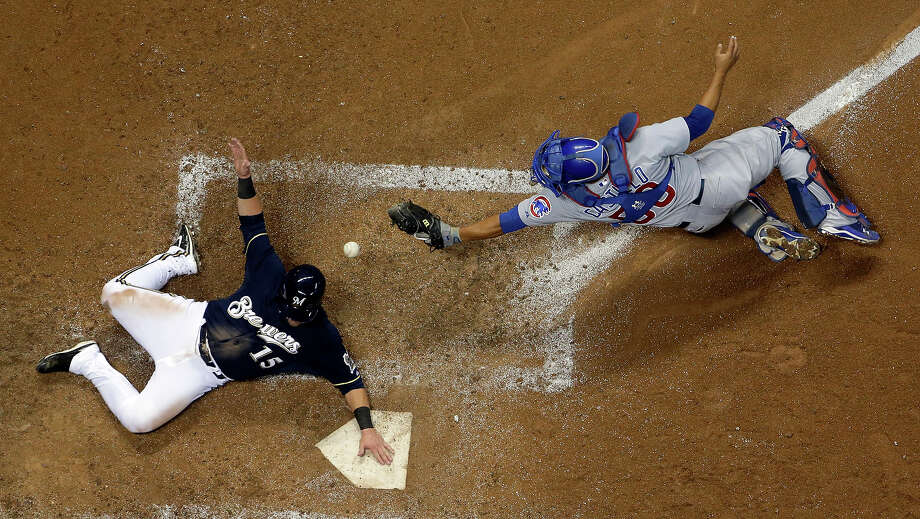 Milwaukee Brewers' Caleb Gindl slides safely past Chicago Cubs catcher Welington Castillo during the sixth inning of a baseball game, Monday, Sept. 16, 2013, in Milwaukee. Gindl scored from second on a hit by Yuniesky Betancourt. Photo: Morry Gash, ASSOCIATED PRESS / AP2013