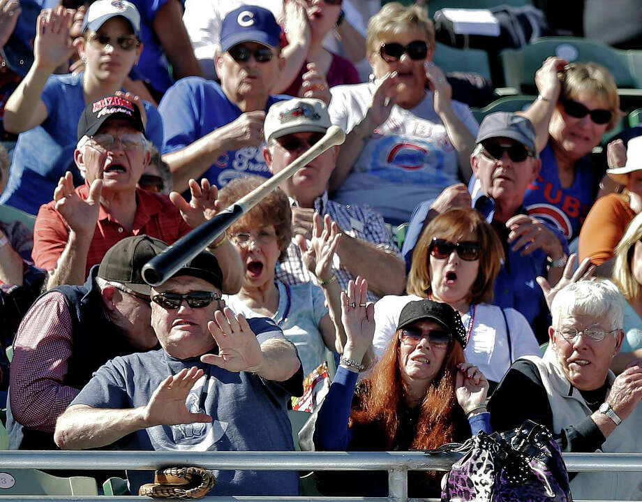 Fans try to get out of the way after Chicago Cubs' Christian Villanueva lost his bat during the fifth inning of an exhibition spring training baseball game against the Colorado Rockies, Tuesday, Feb. 26, 2013, in Phoenix. Photo: Morry Gash, ASSOCIATED PRESS / AP2013