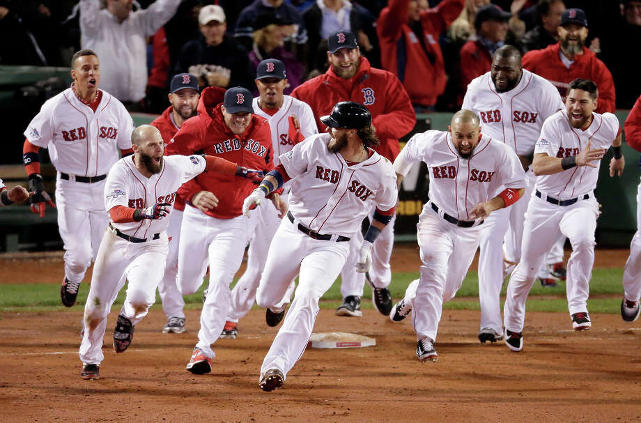 Boston Red Sox players run aftar Jarrod Saltalamacchia after Saltalamacchia hits the game winning single during Game 2 of the American League baseball championship series against the Detroit Tigers Sunday, Oct. 13, 2013, in Boston. The Red Sox won 6-5. Photo: Charlie Riedel, ASSOCIATED PRESS / AP2013