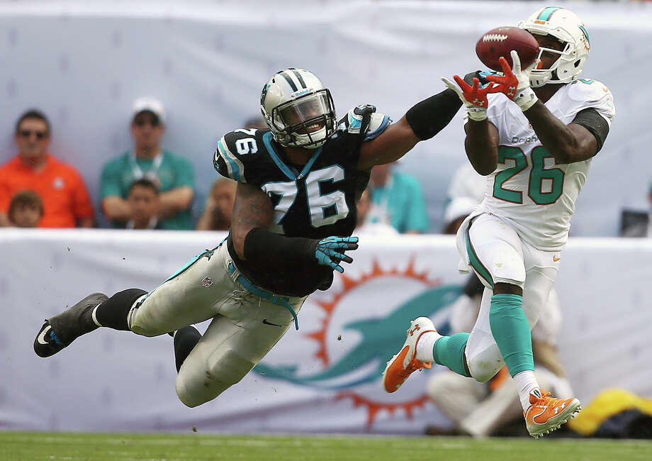 Miami Dolphins running back Lamar Miller (26) grabs a pass as Carolina Panthers defensive end Greg Hardy (76) applies pressure during the first half of an NFL football game on Sunday, Nov. 24, 2013, in Miami Gardens, Fla. Photo: J Pat Carter, ASSOCIATED PRESS / AP2013