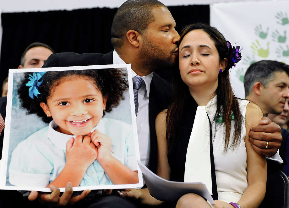 Jimmy Greene, left, kisses his wife Nelba Marquez-Greene as he holds a portrait of their daughter, Sandy Hook School shooting victim Ana  Marquez-Greene at a news conference at Edmond Town Hall in Newtown, Conn., Monday, Jan. 14, 2013. One month after the mass school shooting at Sandy Hook Elementary School, the parents joined a grassroots initiative called Sandy Hook Promise to support solutions for a safer community. Photo: Jessica Hill, ASSOCIATED PRESS / AP2013