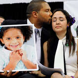 Jimmy Greene, left, kisses his wife Nelba Marquez-Greene as he holds a portrait of their daughter, Sandy Hook School shooting victim Ana  Marquez-Greene at a news conference at Edmond Town Hall in Newtown, Conn., Monday, Jan. 14, 2013. One month after the mass school shooting at Sandy Hook Elementary School, the parents joined a grassroots initiative called Sandy Hook Promise to support solutions for a safer community.
