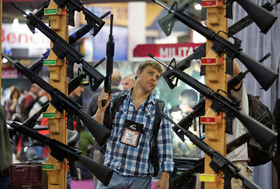 Michael Kiefer, of DeFuniak Springs, Fla., checks out a display of rifles at the Rock River Arms booth during the 35th annual SHOT Show, Thursday, Jan. 17, 2013, in Las Vegas. Photo: Julie Jacobson, ASSOCIATED PRESS / AP2013