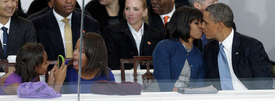 President Barack Obama kisses first lady Michelle Obama as their daughters Sasha, left, and Malia, s
