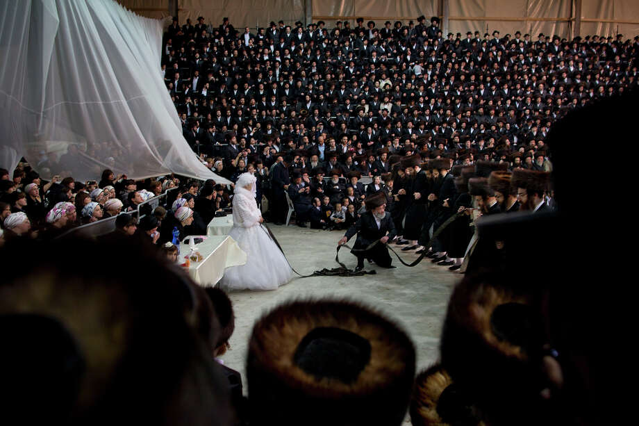 Miryam Teitelbaum, granddaughter of the Ultra-Orthodox Satmar Rebbe of Williamsburg, Rabbi Zalman Leib Teitelbaum, fulfills the Mitzvah tantz during her traditional Jewish wedding in the Israeli town of Beit Shemesh, near Jerusalem, Israel, early Thursday, Jan. 24, 2013. The bride enters to the men's section to fulfill the Mitzvah tantz, in which family members and honored rabbis are invited to dance in front of the bride, often holding a gartel, and then dancing with the groom. Photo: Oded Balilty, ASSOCIATED PRESS / AP2013