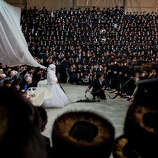 Miryam Teitelbaum, granddaughter of the Ultra-Orthodox Satmar Rebbe of Williamsburg, Rabbi Zalman Leib Teitelbaum, fulfills the Mitzvah tantz during her traditional Jewish wedding in the Israeli town of Beit Shemesh, near Jerusalem, Israel, early Thursday, Jan. 24, 2013. The bride enters to the men's section to fulfill the Mitzvah tantz, in which family members and honored rabbis are invited to dance in front of the bride, often holding a gartel, and then dancing with the groom.