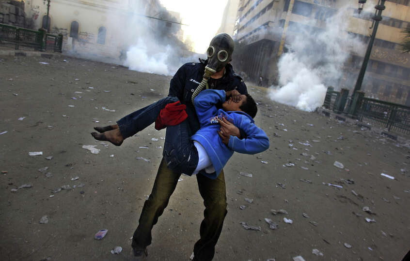 An Egyptian protester evacuates an injured boy during clashes near Tahrir Square, Cairo, Egypt, Frid