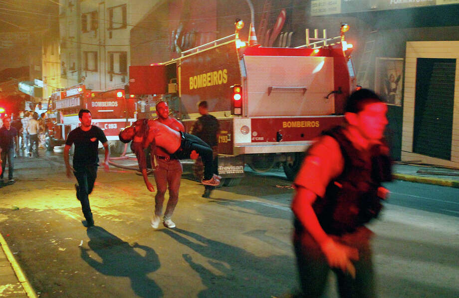 A man carries an injured victim of a fire at the Kiss  club in Santa Maria city,  Rio Grande do Sul state,  Brazil, early Sunday, Jan. 27, 2013. Photo: Uncredited, ASSOCIATED PRESS / AP2013