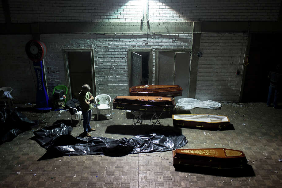 A man stands around coffins containing the remains of victims after the bodies were identified at a gymnasium in Santa Maria city, Rio Grande do Sul state, Brazil, Sunday, Jan. 27, 2013. A fast-moving fire roared through the crowded, windowless Kiss nightclub in southern Brazil, within seconds filling the space with flames and a thick, toxic smoke that killed more than 230 panicked partygoers who gasped for breath and fought in a stampede to escape. Photo: Felipe Dana, ASSOCIATED PRESS / AP2013