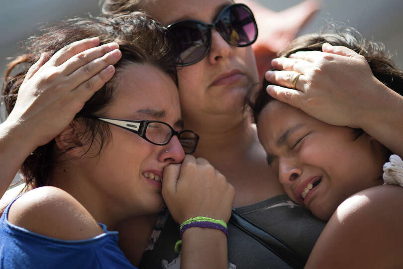 Girls cry in front of a makeshift memorial outside the Kiss nightclub where a fire killed over 230 p