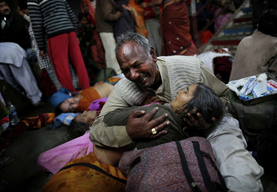 An Indian man weeps as he holds his wife who was killed in a stampede on a railway platform at the main railway station in Allahabad, India, Sunday, Feb. 10, 2013. Photo: Kevin Frayer, ASSOCIATED PRESS / A2013