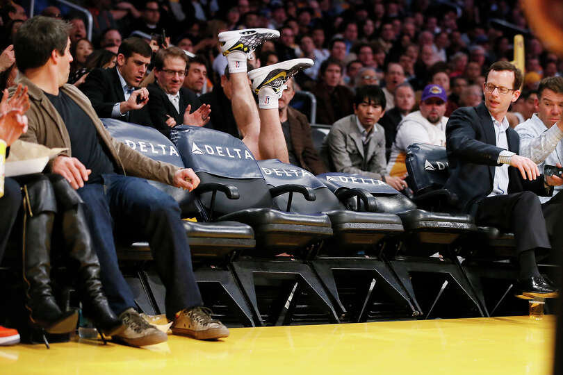 Los Angeles Lakers' Steve Blake falls over empty courtside chairs as he tries to save a ball from go