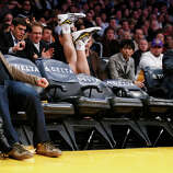 Los Angeles Lakers' Steve Blake falls over empty courtside chairs as he tries to save a ball from going out of bounds against the Phoenix Suns during the first half of an NBA basketball game on Tuesday, Feb. 12, 2013, in Los Angeles.