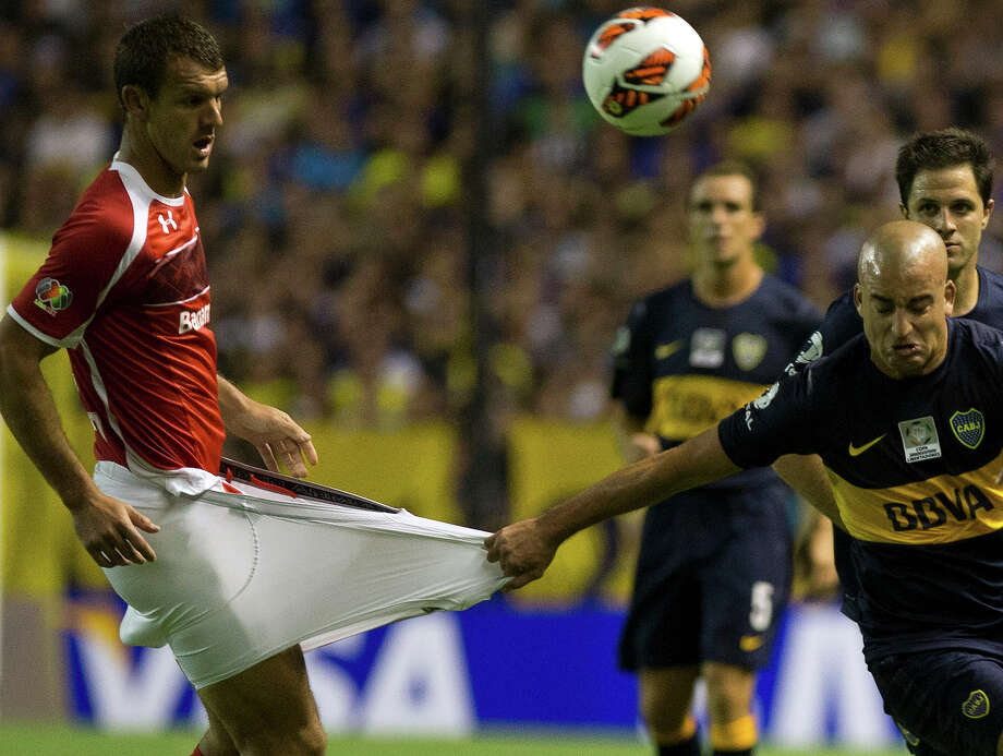 Argentina's Boca Juniors' Santiago Silva, right, grabs Mexico's Toluca's Diego Novaretti during a Copa Libertadores soccer match in Buenos Aires, Argentina, Wednesday, Feb. 13, 2013. Photo: Eduardo Di Baia, ASSOCIATED PRESS / AP2013