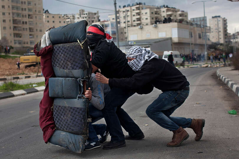 Masked Palestinians use a back car seat as a shield during a protest to support Palestinian prisoner