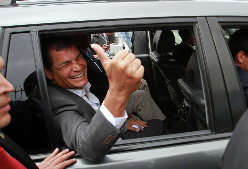 President Rafael Correa gives a thumbs-up as he leaves a polling station after voting in Quito, Ecua