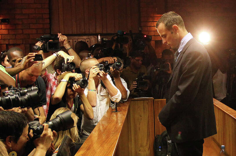 Photographers take photos of Olympic athlete Oscar Pistorius as he stands in the dock during his bai