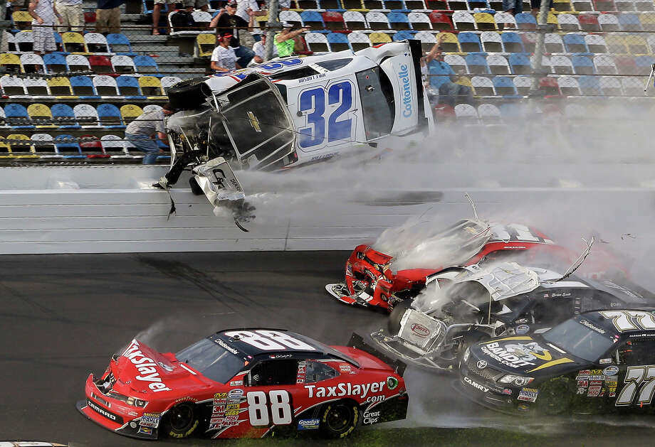 Kyle Larson (32) goes airborne and into the catch fence in a multi-car crash involving Dale Earnhardt Jr. (88), Parker Kilgerman (77), Justin Allgaier (31) and Brian Scott (2) during the final lap of the NASCAR Nationwide Series auto race at Daytona International Speedway, Saturday, Feb. 23, 2013, in Daytona Beach, Fla. Photo: John Raoux, ASSOCIATED PRESS / The Associated Press2013