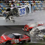 Kyle Larson (32) goes airborne and into the catch fence in a multi-car crash involving Dale Earnhardt Jr. (88), Parker Kilgerman (77), Justin Allgaier (31) and Brian Scott (2) during the final lap of the NASCAR Nationwide Series auto race at Daytona International Speedway, Saturday, Feb. 23, 2013, in Daytona Beach, Fla.