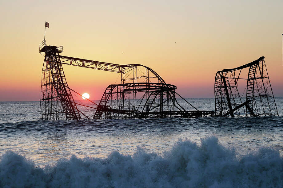 The sun rises in Seaside Heights, N.J., Monday, Feb. 25, 2013, behind the Jet Star Roller Coaster which has been sitting in the ocean after part of the Funtown Pier was destroyed during Superstorm Sandy. The private owners of the amusement pier that collapsed in Seaside Heights were working with insurers to devise a plan to dismantle the ride and get it out of the ocean. Photo: Mel Evans, ASSOCIATED PRESS / AP2013
