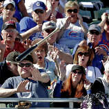 Fans try to get out of the way after Chicago Cubs' Christian Villanueva lost his bat during the fifth inning of an exhibition spring training baseball game against the Colorado Rockies, Tuesday, Feb. 26, 2013, in Phoenix.