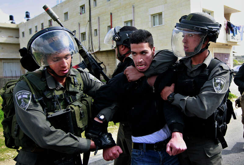 Isreali border policemen arrest a Palestinian man during a protest to support Palestinian prisoners,