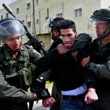 Isreali border policemen arrest a Palestinian man during a protest to support Palestinian prisoners, outside Ofer, an Israeli military prison near the West Bank city of Ramallah, Thursday, Feb. 28, 2013.