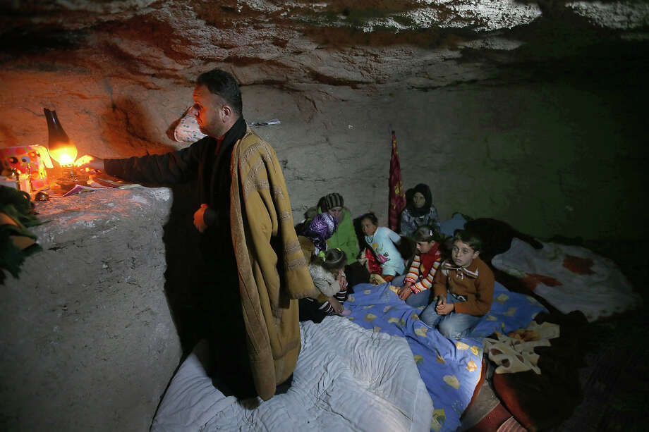 A defected Syrian policeman, Adnan al-Hamod, 33, lights a kerosene lamp at an underground cave used for shelter from Syrian government forces shelling and airstrikes, at Jirjanaz village, in Idlib province, Syria, Thursday Feb. 28, 2013. Across northern Syria, rebels, soldiers, and civilians are making use of the country's wealth of ancient and medieval antiquities to protect themselves from Syria's two-year-old war. They are built of thick stone that has already withstood centuries, and are often located in strategic locations overlooking towns and roads. Photo: Hussein Malla, ASSOCIATED PRESS / AP2013