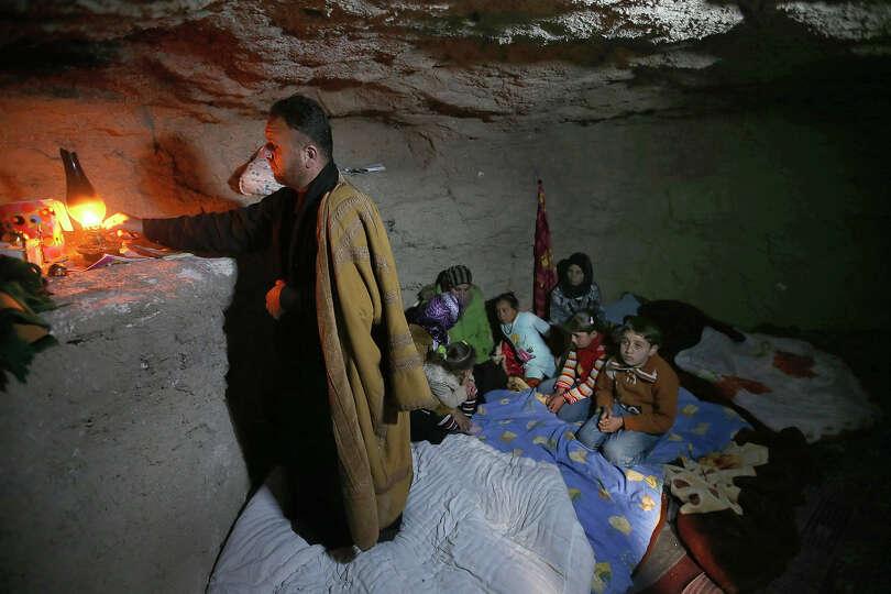 A defected Syrian policeman, Adnan al-Hamod, 33, lights a kerosene lamp at an underground cave used