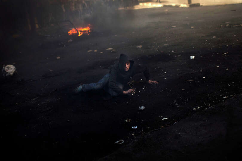 A Palestinian stone-thrower lays on the ground during clashes with Israeli forces, not pictured, in