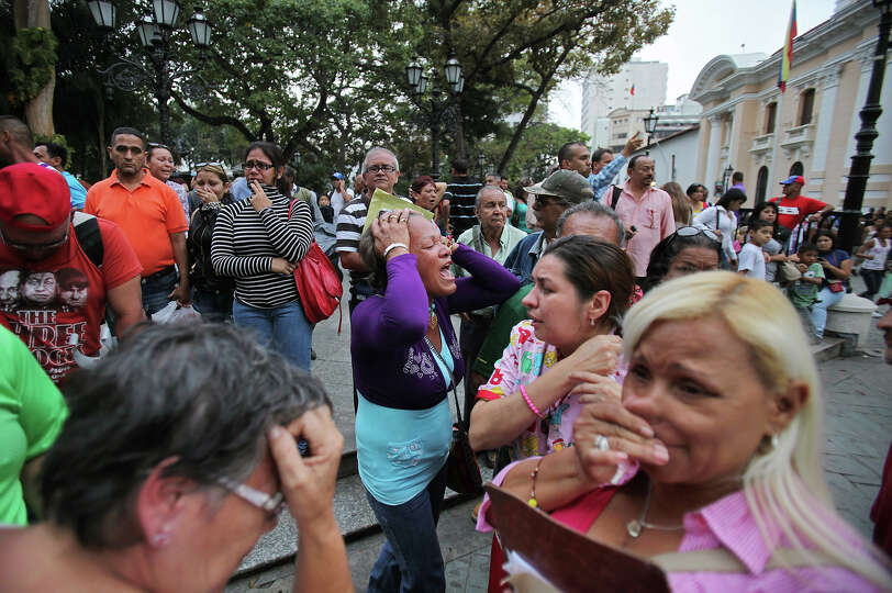 Supporters of Venezuela's President Hugo Chavez react after the vice president announced Chavez's de
