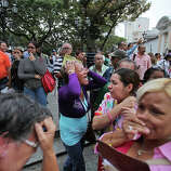 Supporters of Venezuela's President Hugo Chavez react after the vice president announced Chavez's death in downtown Caracas, Venezuela, Tuesday, March 5, 2013. Venezuela's Vice President Nicolas Maduro announced that Chavez died on Tuesday at age 58 after a nearly two-year bout with cancer.