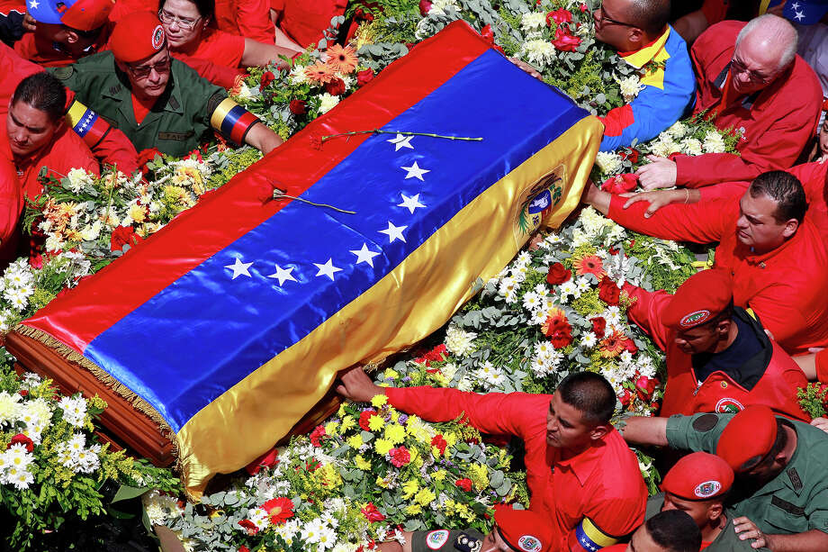 The flag-draped coffin containing the body of Venezuela's late President Hugo Chavez is taken from the hospital where he died, to a military academy, where it will remain until his funeral in Caracas, Venezuela, Wednesday, March 6, 2013. Seven days of mourning were declared, all schools were suspended for the week and friendly heads of state were expected for an elaborate funeral. Photo: Ricardo Mazalan, ASSOCIATED PRESS / AP2013