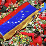 The flag-draped coffin containing the body of Venezuela's late President Hugo Chavez is taken from the hospital where he died, to a military academy, where it will remain until his funeral in Caracas, Venezuela, Wednesday, March 6, 2013. Seven days of mourning were declared, all schools were suspended for the week and friendly heads of state were expected for an elaborate funeral.