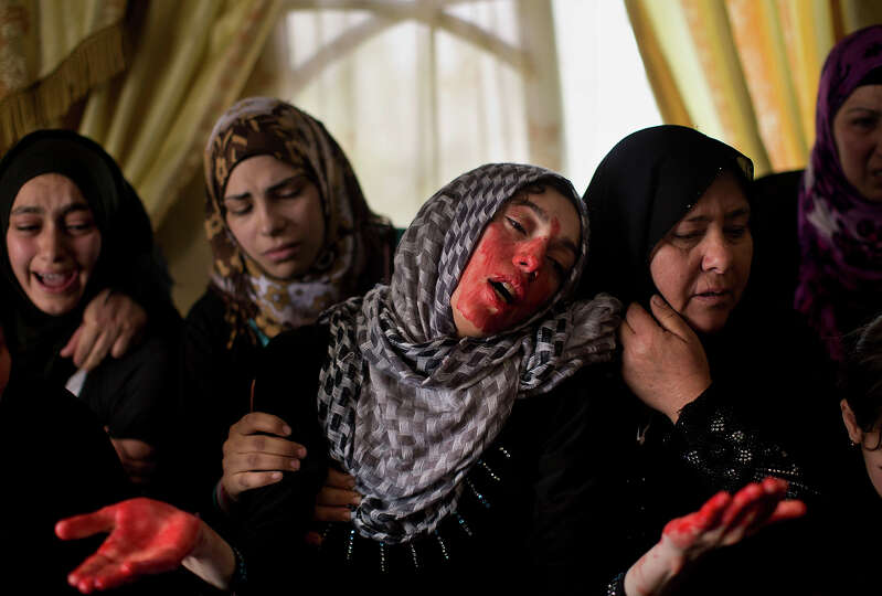 Faheema Titi, the sister of Palestinian Mahmoud Titi is covered with the blood of her dead brother a
