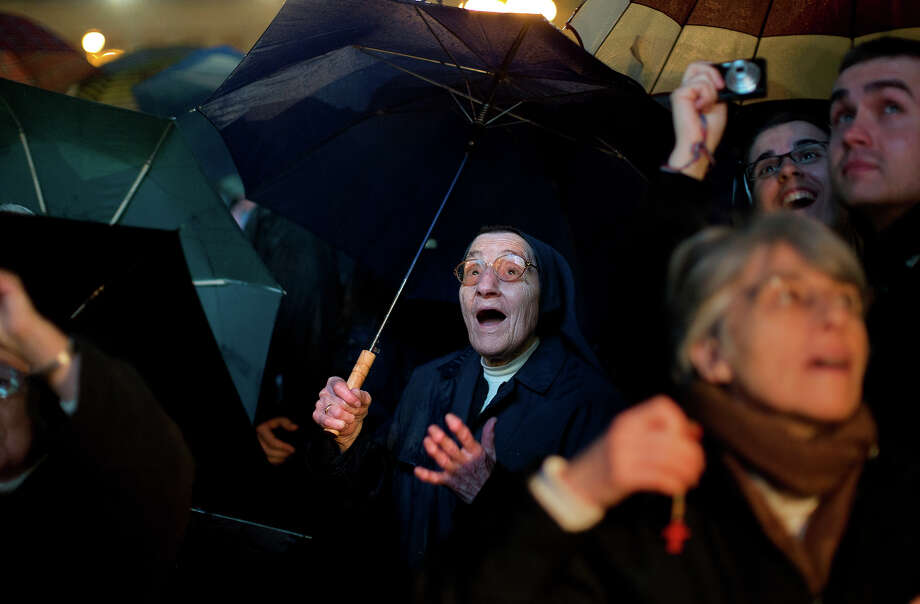 A nun reacts after white smoke billowed from the chimney on the Sistine Chapel indicating that a new pope has been elected in St. Peter's Square at the Vatican, Wednesday, March 13, 2013. Argentine Cardinal Jorge Bergoglio, who chose the name of Pope Francis, is the 266th pontiff of the Roman Catholic Church. Photo: Emilio Morenatti, ASSOCIATED PRESS / The Associated Press2013