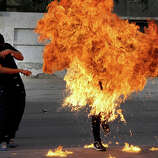 """A Bahraini anti-government protester is engulfed in flames when a shot fired by riot police hit the petrol bomb in his hand that he was preparing to throw during clashes in Sanabis, Bahrain, Thursday, March 14, 2013. Protests and clashes erupted in opposition areas nationwide with government opponents observing a """"Dignity Strike"""" blocking roads, closing shops, protesting and staying home from work and school called by the more radical February 14 youth group."""