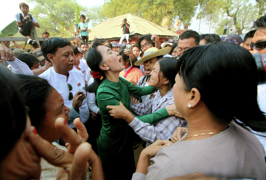 Myanmar opposition leader Aung San Suu Kyi talks with crying villagers during a visit to Tone village, an area near the Letpadaung copper mine project, in Monywa, 760 kilometers (450 miles) north of Yangon, central Myanmar, Thursday, March 14, 2013. Suu Kyi met with rare public scorn while trying to justify an official report endorsing continued operation of the copper mine in northwestern Myanmar opposed by many local residents. Photo: Khin Maung Win, ASSOCIATED PRESS / A2013