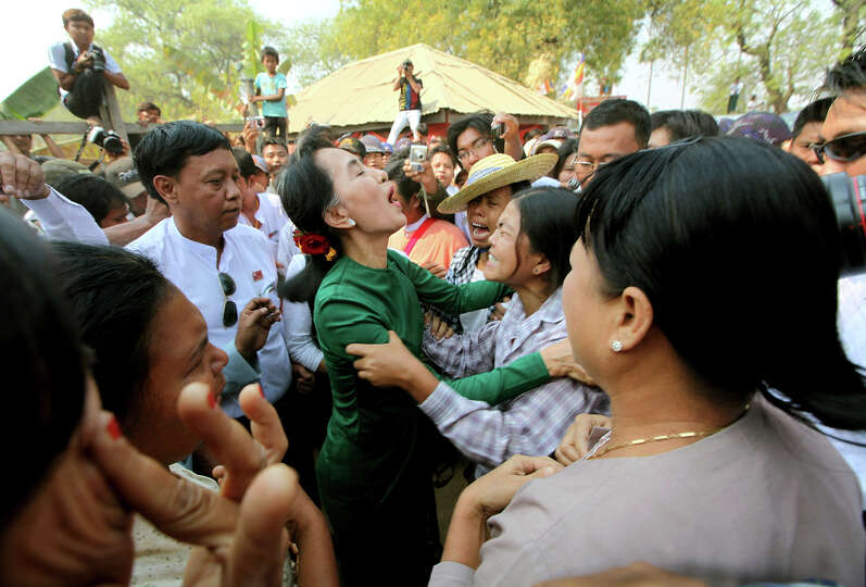 Myanmar opposition leader Aung San Suu Kyi talks with crying villagers during a visit to Tone villag