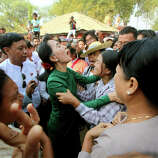 Myanmar opposition leader Aung San Suu Kyi talks with crying villagers during a visit to Tone village, an area near the Letpadaung copper mine project, in Monywa, 760 kilometers (450 miles) north of Yangon, central Myanmar, Thursday, March 14, 2013. Suu Kyi met with rare public scorn while trying to justify an official report endorsing continued operation of the copper mine in northwestern Myanmar opposed by many local residents.