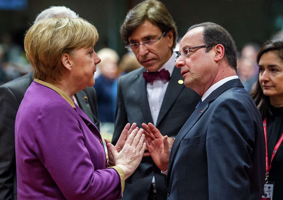 German Chancellor Angela Merkel, second left, speaks with French President Francois Hollande, second right, during a round table meeting at an EU summit in Brussels on Friday, March 15, 2013. Photo: Geert Vanden Wijngaert, ASSOCIATED PRESS / A2013