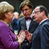 German Chancellor Angela Merkel, second left, speaks with French President Francois Hollande, second right, during a round table meeting at an EU summit in Brussels on Friday, March 15, 2013.