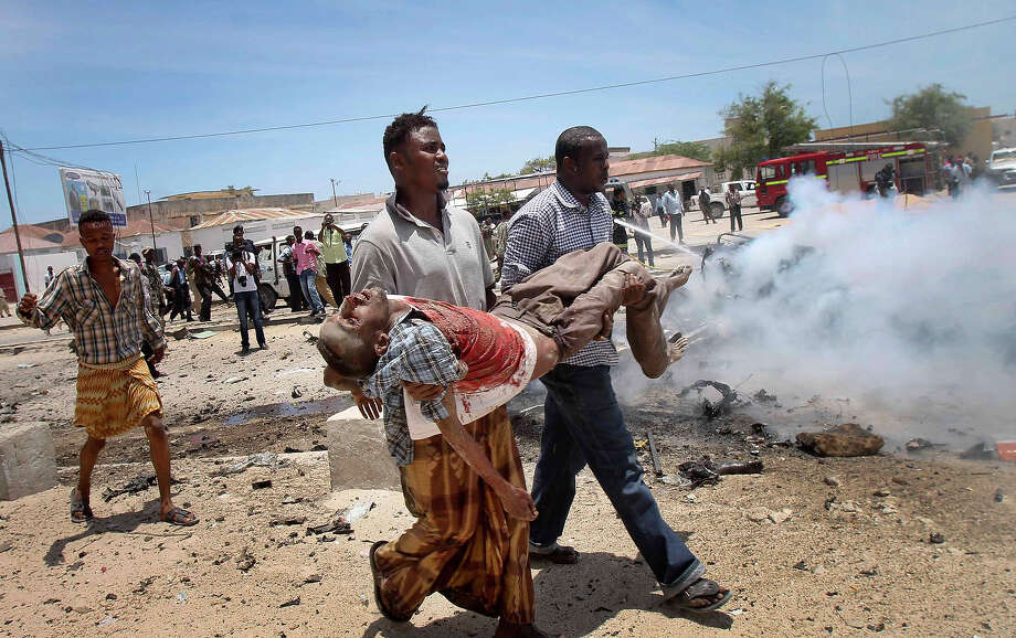 Somali men carry a seriously wounded man after a car bomb blast close to the Somali government's headquarters in the capital Mogadishu, Somalia Monday, March 18, 2013. An explosives-laden car that apparently was targeting a truck full of Somali government officials instead hit a civilian car and exploded, setting a nearby mini-bus on fire and killing at least seven people. Photo: Farah Abdi Warsameh, ASSOCIATED PRESS / AP2013