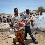 Somali men carry a seriously wounded man after a car bomb blast close to the Somali government's headquarters in the capital Mogadishu, Somalia Monday, March 18, 2013. An explosives-laden car that apparently was targeting a truck full of Somali government officials instead hit a civilian car and exploded, setting a nearby mini-bus on fire and killing at least seven people.