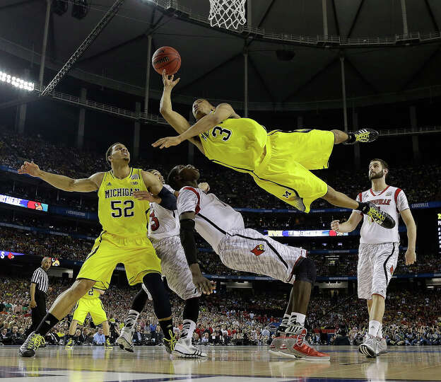 Michigan guard Trey Burke (3) shoots over Louisville center Gorgui Dieng (10) during the second half
