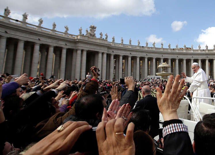 Pope Francis waves to faithful as he is driven through the crowd in his popemobile in St. Peter's Sq