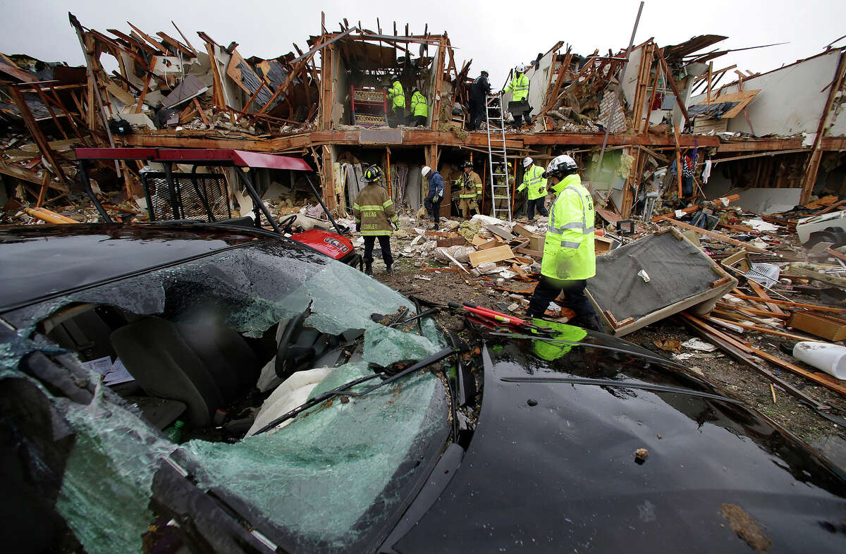A smashed car sits in front of an apartment complex destroyed by an explosion at a fertilizer plant in West, Texas, as firefighters conduct a search and rescue Thursday, April 18, 2013. A massive explosion occured at the West Fertilizer Co.