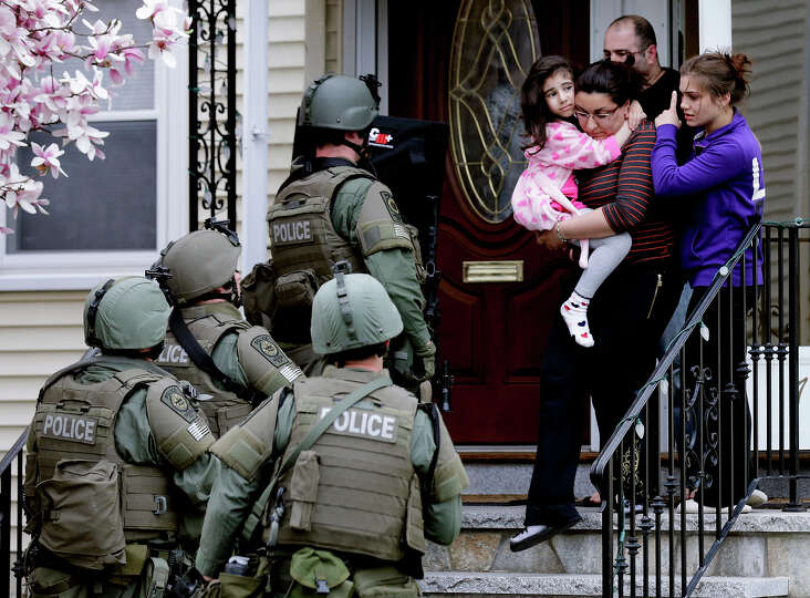 A woman carries a girl from their home as a SWAT team searching for a suspect in the Boston Marat