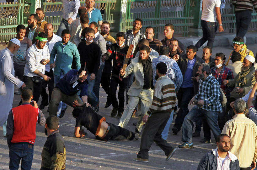 Muslim Brotherhood supporters beat a protester in Tahrir Square, as supporters and opponents of Egyp